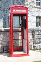 Telephone booth in front of a stone building.