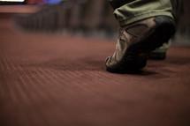 feet of a man walking down the aisle of a church