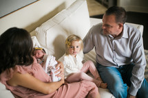 father and mother on a couch holding an infant and toddler girl