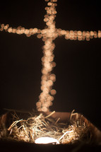 bokeh Christmas lights in the shape of a cross over a glowing manger