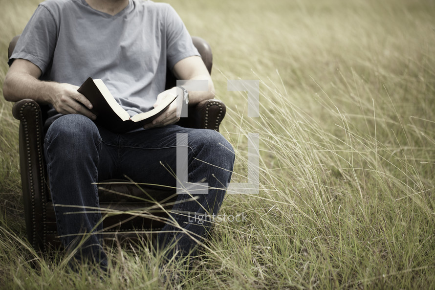 A young man studies the Bible in a grassy field.