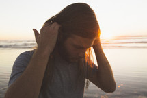 a man tucking his long hair behind his ears on a beach