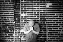 A man praying against a brick wall
