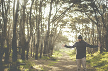a man standing in a forest with outstretched arms