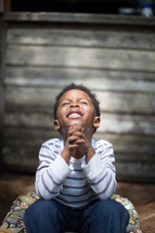 toddler boy with praying hands looking up to God