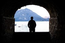 silhouette of a man standing in a tunnel and looking out at a lake