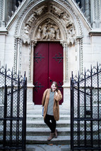 A woman posing in front of Cathedral doors in France