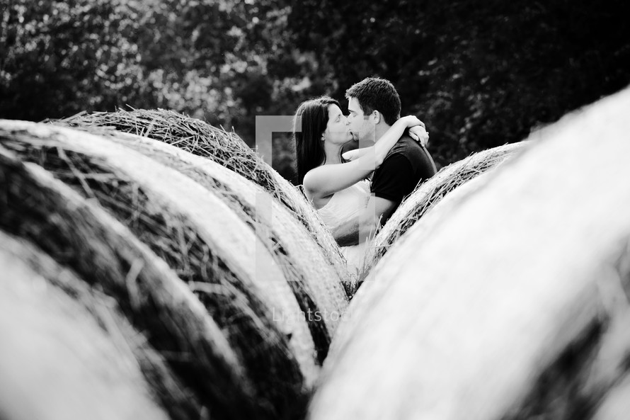 Man and woman kissing behind hay rolls