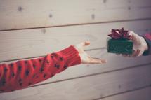 a man handing a woman a Christmas present