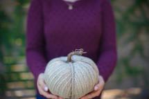 a woman holding a burlap pumpkin