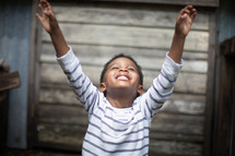 a toddler boy with raised hands