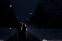 Silhouette of a couple kissing in the snowfall at night.