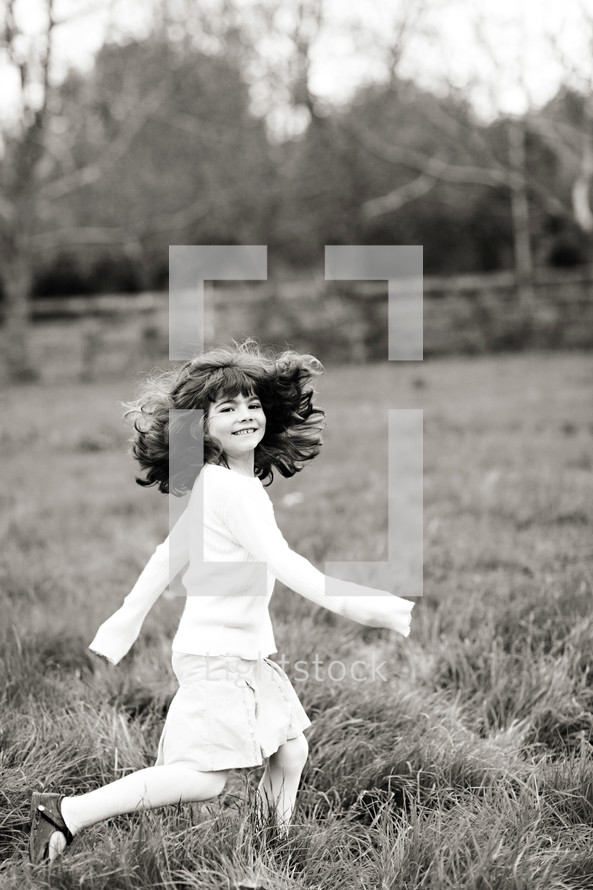 young girl running in grass field, dress, hair, smile.