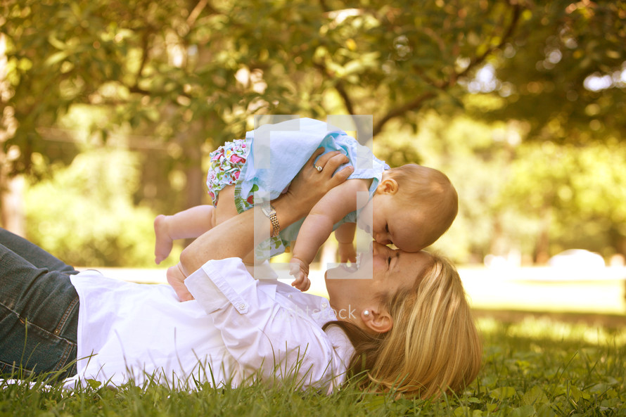 A mother and child playing in the grass.