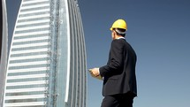 engineer with a hardhat standing in front of a high-rise building