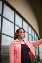 African-American woman welcoming others at the entrance of a church