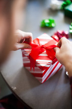 Hands tying a bow on a red and white Christmas present