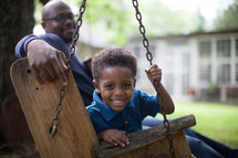 A father and son sitting in a swing in the back yard.