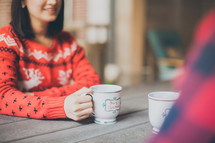 woman in a Christmas sweater holding a Merry Christmas coffee cup