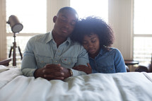 a couple in prayer at the side of a bed