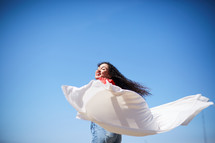 a woman with outstretched arms holding a white sheet