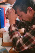 a man sitting at his desk reading a Bible and praying