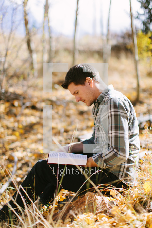 Man Reading and studying the Bible during Fall