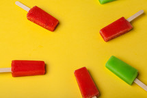 Red and green popsicles arranged on a yellow background.