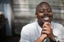 a smiling African American man with praying hands