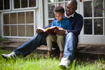 Father and son sitting together and reading the Bible.