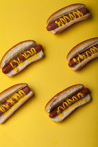 Hot dogs and buns drizzled with mustard on a bright yellow background.