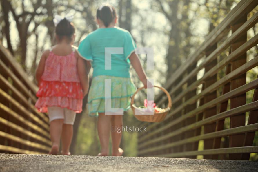 Sisters walking over bride carrying basket of flowers