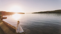 a bride standing by a lake shore at sunset