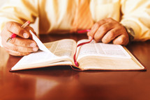 Hands holding a pen on the Bible.
