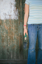 Teen holding a spade shovel near a half painted fence.