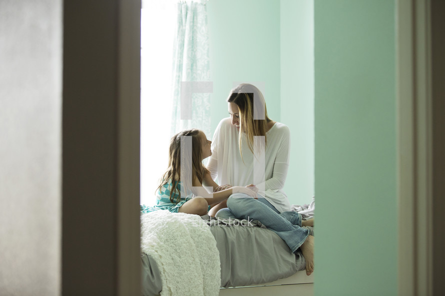 mother and daughter talking on a bed