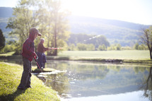 a grandson and grandfather fishing in a pond