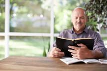 a man reading a Bible on a porch