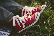 a child's red sneakers in the grass