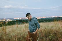 a man walking through a field of tall grasses