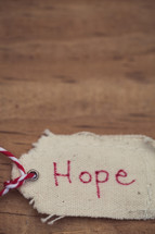 """A Christmas gift tag reading """"Hope,"""" on a wood grain background."""