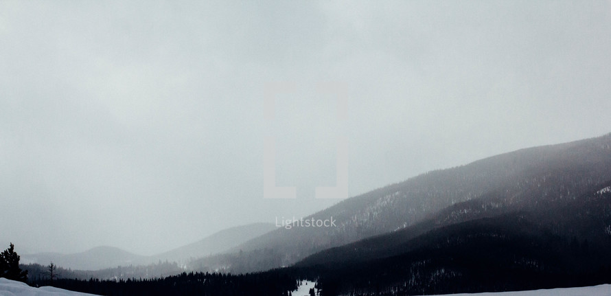 fog over a snowy mountain