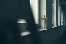 sunlight through a window shining on a cross in a church