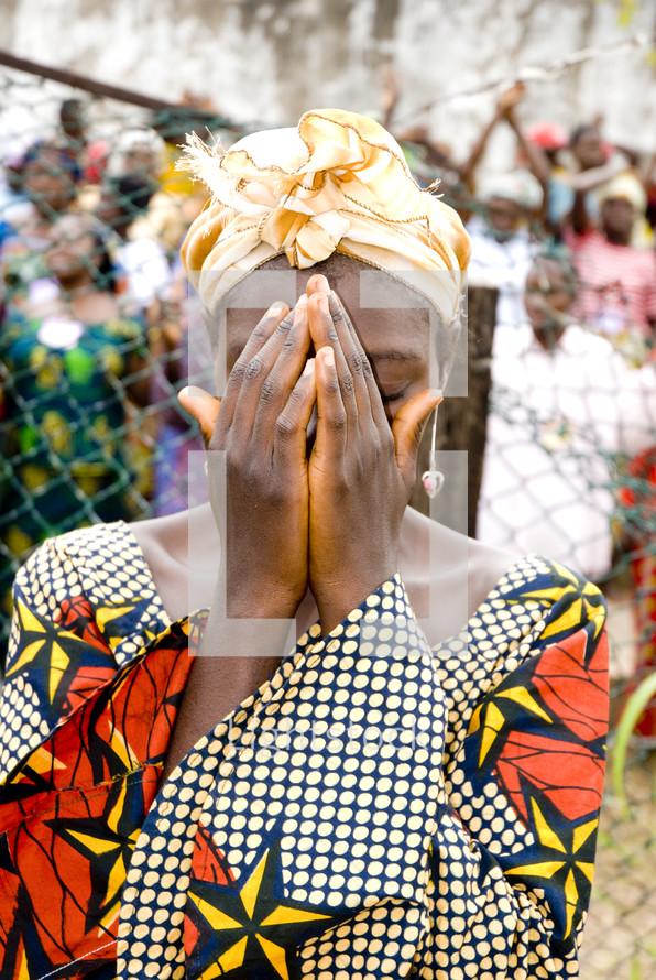 An African woman in tribal dress in prayer