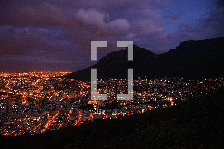 Night Time and City Lights at the foot of a mountain range