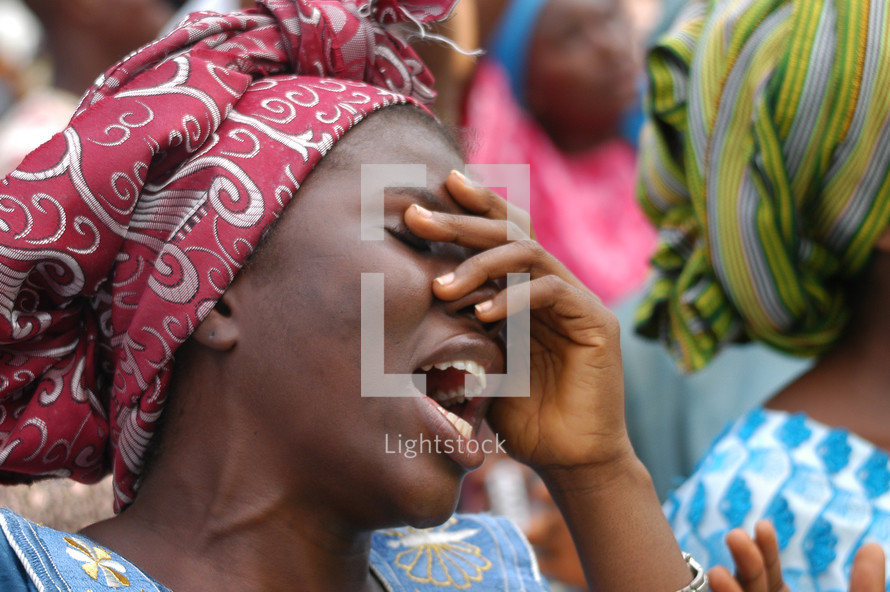 Woman praising God with hand over her face