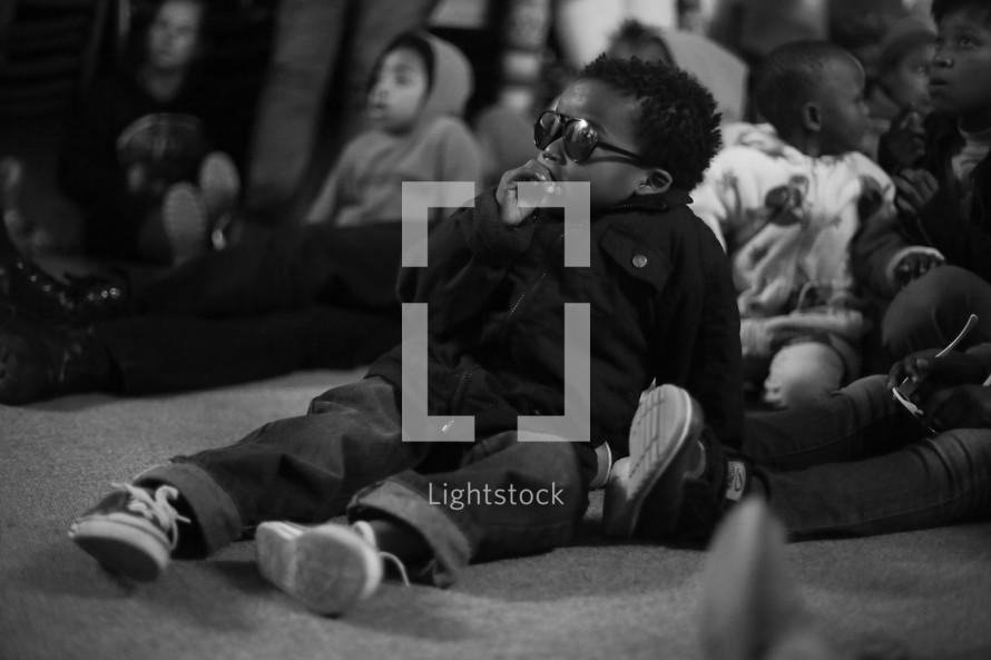 Little boy wearing sunglasses amongst group of sitting children