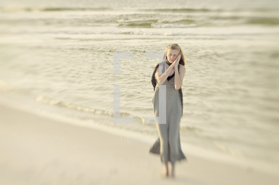 woman in prayer to God on a beach