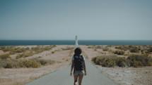 a woman walking down a road towards a shore