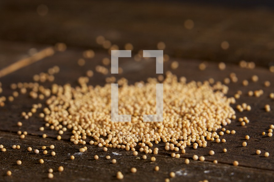 Scattered mustard seeds on wood table
